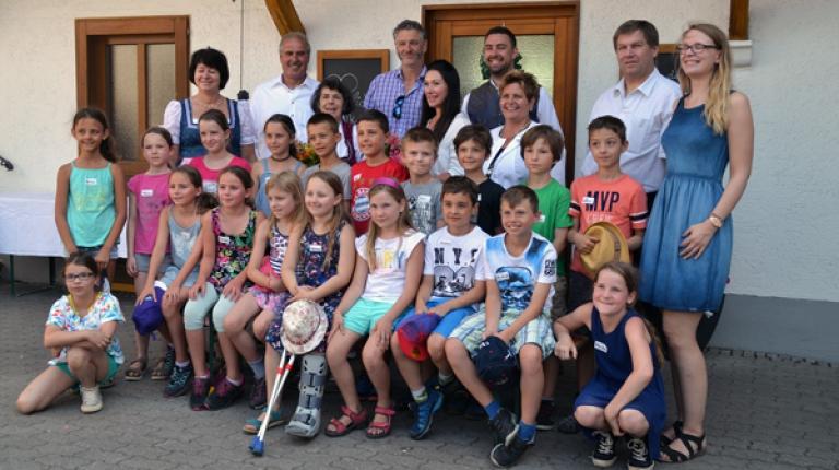 """Schirmherr des Kindertags auf bayerischen Bauernhöfen 2017 ist Radiomoderator Bernhard """"Fleischi"""" Fleischmann (2.v.l. hinten), der sich mit den Kindern zum Gruppenbild aufgestellt hat."""