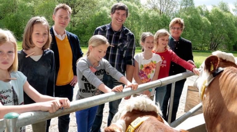 Neben den Kindern auf dem Bild: Holger Stromberg, Koch der deutschen Fußballnationalmannschaft (hinten links), Anton Lohmeier, Junior vom Hof in Unterthalham (Mitte) und Landesbäuerin Anneliese Göller.