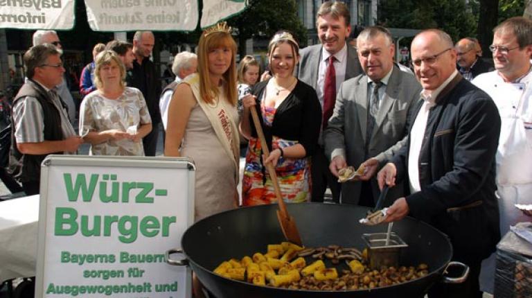 """""""Mit unserer Arbeit sorgen wir für Ausgewogenheit und die richtige Würze."""" Zusammen mit anderen Landwirten grillte Präsident Heidl er in der Würzburger Innenstadt Fleisch und Gemüse und verteilte leckere """"Würz-Burger""""."""